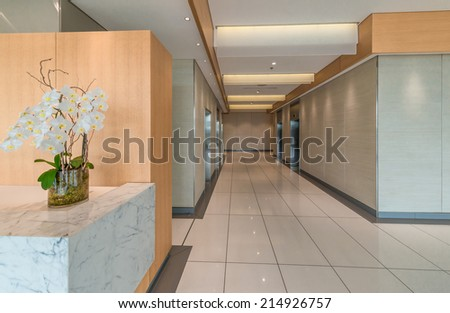 Marble counter with some flowers of the modern lobby, hallway of the luxury hotel, business center, shopping mall in Vancouver, Canada. Interior design. - stock photo