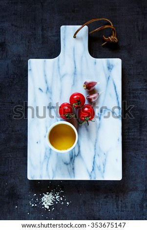 Marble cutting board and healthy ingredients for tasty vegetarian cooking. Diet or vegan food concept. Top view. - stock photo