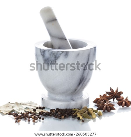 Marble mortar and pestle with black pepper and assorted spices on white background - stock photo
