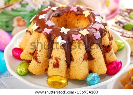 marble ring cake with chocolate sauce and  colorful butterfly shape sprinkles for easter - stock photo