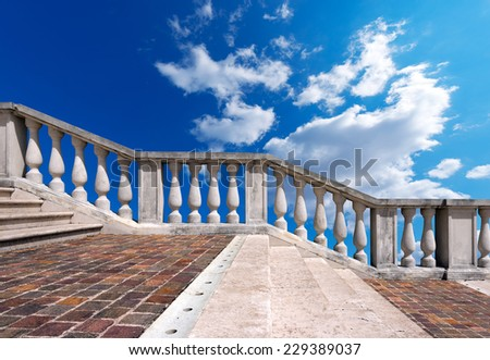 Marble Staircase on Blue Sky with Clouds / Staircase in white stone and marble with balustrade on blue sky with clouds - stock photo
