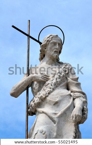 Marble statue of St. John the baptist against the blue sky. - stock photo