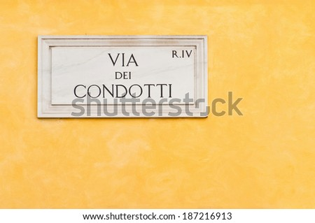 marble street plate of the famous Via dei Condotti in Rome, Italy. It is a fashionable street next to the Spanish Steps, constantly packed with tourists, shoppers and locals. - stock photo
