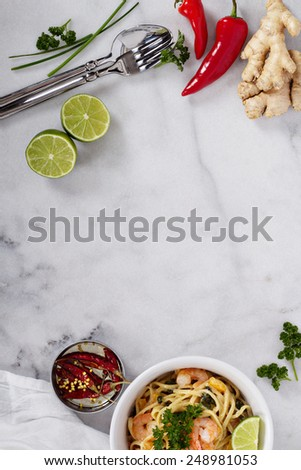 Marble table with asian cooking ingredients and shrimp pasta - stock photo