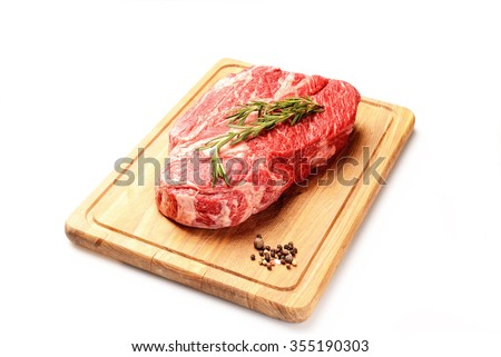 marble veal steak with rosemary on a board on a white background - stock photo
