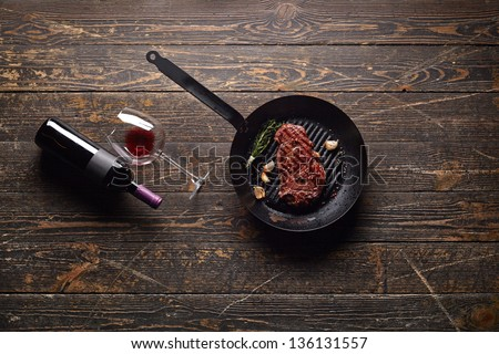 Marbled beef steak in a grill pan with a bottle of wine and wine glass on old wood background. Juicy food background. - stock photo