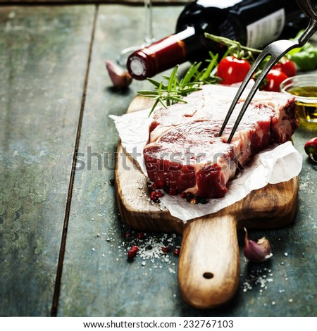 Marbled beef steak  with a bottle of wine and vegetables on old wood background - stock photo