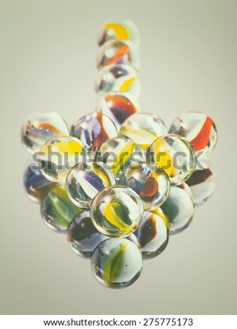 Marbles in arrow shape on reflective surface pointing at viewer, vintage toned - stock photo