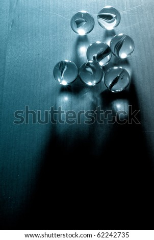 Marbles in Single Point Lighting with Blue Filter - stock photo