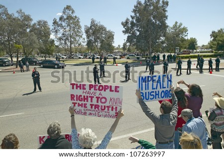 MARCH 2005 - Presidential Motorcade with President George W. Bush past anti-Bush political rally with signs that read Impeach Bush in Tucson, AZ - stock photo
