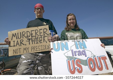 MARCH 2005 - Three protestors in Tucson, AZ of President George W. Bush is holding a sign proclaiming Bush is a Liar and US Out regarding the Iraq War - stock photo