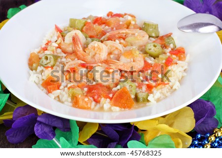 Mardi Gras decorations surround a full plate of fresh, homemade shrimp gumbo. - stock photo