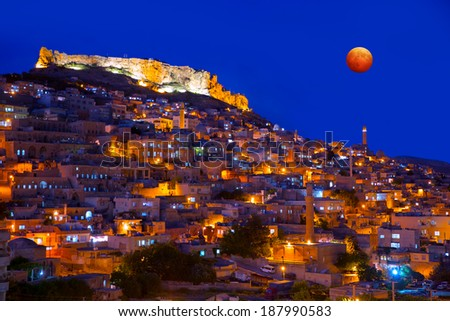 Mardin old town and lunar eclipse - stock photo