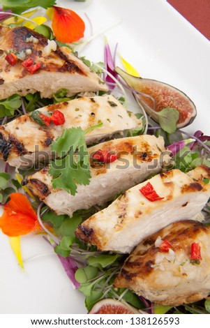Margarita Chicken breast, grilled, over Micro Greens salad with edible flowers and black figs.  - stock photo