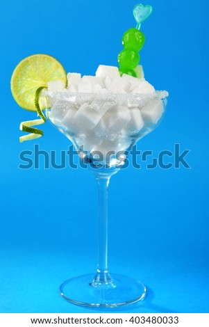 Margarita glass with lump sugar, cocktail cherries and lime slice on blue background - stock photo