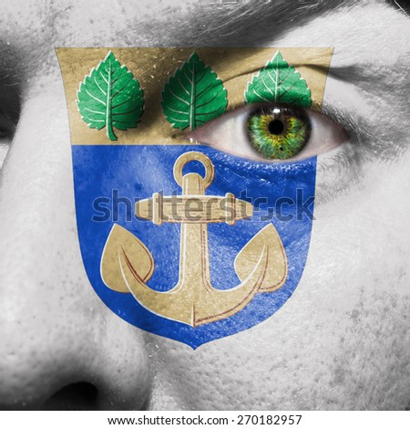 Mariehamn flag painted on a man's face to support his city Mariehamn - stock photo