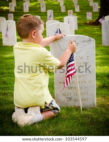 MARIETTA, GA - MAY 26: An unidentified boy straightens a flag on a veteran's grave on May 26, 2012, for Memorial Day Weekend at the National Cemetery in Marietta, Ga. - stock photo