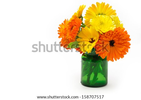 Marigold flowers bouquet in  green glass - stock photo