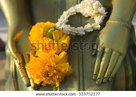 Marigold garland on hands of buddha statue at Wat Arun temple in Thailand - stock photo
