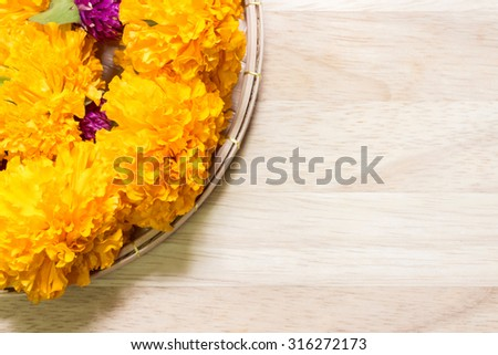 Marigolds and globe amaranth on wooden background ; part of Thai garlands - stock photo