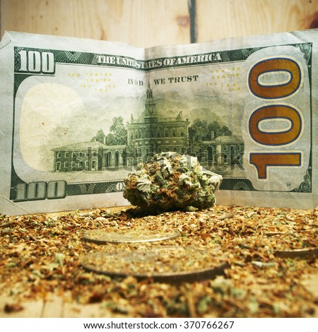 Marijuana Buds and Hundred Dollar Bills, Cannabis and Money Representing the Legal American Marijuana Industry  - stock photo