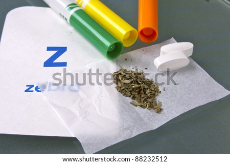 marijuana in paper with crayons in background - stock photo