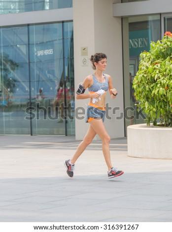 Marina bay, Singapore - Sep 9: Woman running on road for health. on Sep 9, 2015 in Marina bay,Singapore. - stock photo