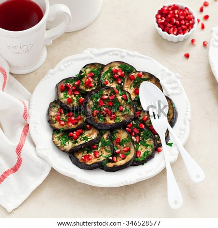 Marinated baked eggplant salad with cilantro, garlic and pomegranate seeds, selective focus - stock photo