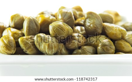 Marinated capers on a white plate , isolated on white - stock photo
