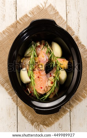 marinated chicken drumstick with red peppers, onion, garlic and rosemary in a black slow cooker - stock photo