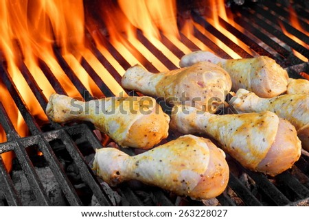 Marinated Chicken Legs On The Hot Barbecue Grill. Flame Of Fire On The Background. - stock photo
