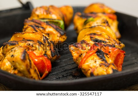 marinated chicken meat skewers with onions and peppers smoking on the grill pan  - stock photo