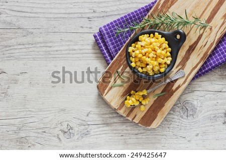 marinated corn in a bowl on a cutting board and rosemary on a wooden background. home preservation. top view. copy space background - stock photo