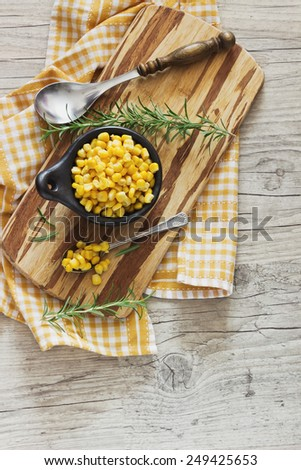 marinated corn in a bowl on a cutting board and rosemary on a wooden background. home preservation. top view. - stock photo