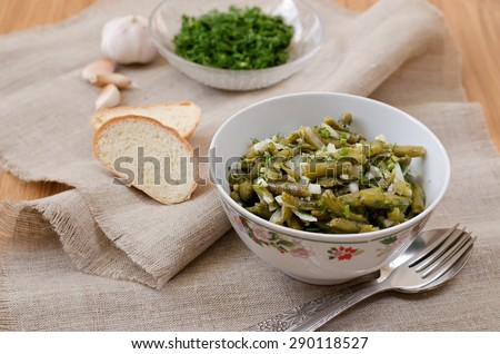 Marinated green beans with onions, garlic, dill. Cooked with olive oil. - stock photo