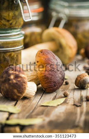 Marinated mushrooms in jars on a wooden table - stock photo