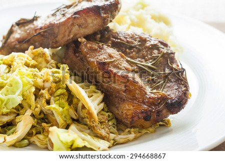 Marinated pork chops on a bed of savoy cabbage - stock photo