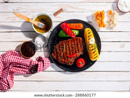 Marinated spicy grilled rib eye beef steak served on a metal skillet with barbecued peppers and corn on the cob on an outdoor white wooden table, overhead view - stock photo