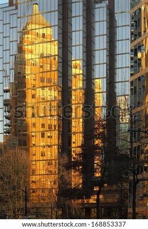 Marine Building Vancouver Reflection. Vancouver's old reflected in it's new. The historic Marine Building, in downtown Vancouver, is reflected in the glass of a modern office tower.  - stock photo