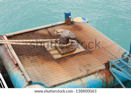 Marine Rope tied around steel post on pier on koh samui - stock photo