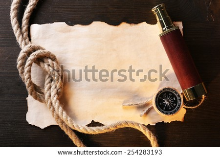 Marine still life spyglass, compass rope and sheet of paper on wooden background - stock photo