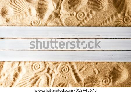 Marine template of three wooden planks on sand. - stock photo