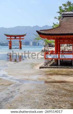 Marine tide at Itsukushima Shinto shrine, the sacred red torii in shallow water. Miyajima Island, Japan - stock photo
