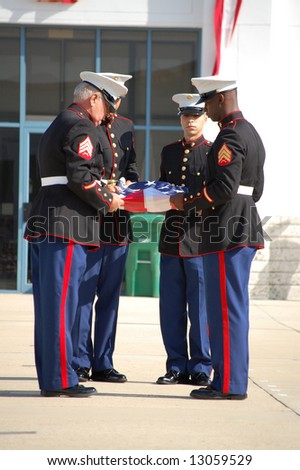 Marines folding American flag at Memorial Day ceremony - stock photo