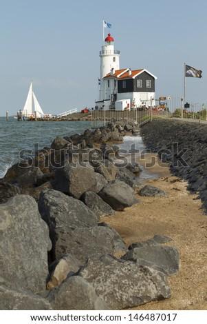 "MARKEN - JULY 15: A sailboat sails past the ""Paard van Marken"" lighthouse in Marken, the Netherlands, on July 15, 2013. - stock photo"