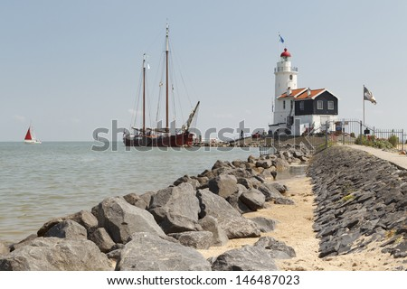 "MARKEN - JULY 15: An old wooden sailboat visits the ""Paard can Marken"" lighthouse in Marken, the Netherlands, on July 15, 2013. - stock photo"