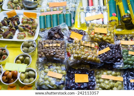 Market counter with tasty olives and olive products - stock photo