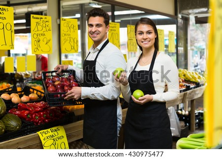 Market workers with assortment of fruits, prices on Spanish - stock photo