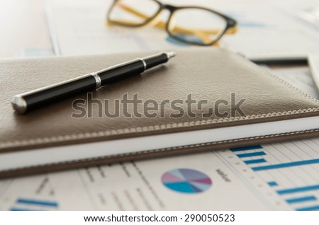 Marketer's desk with analysis Report , pen,book. - stock photo
