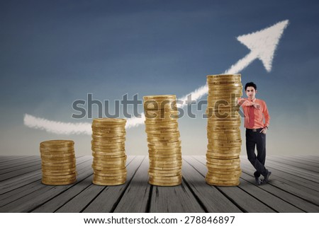 Marketing agent and rising gold coins chart with blue sky background - stock photo